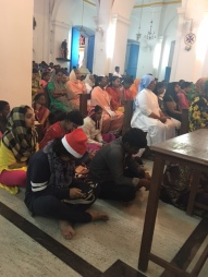 Locals attending mass on the floor as the seats are filled